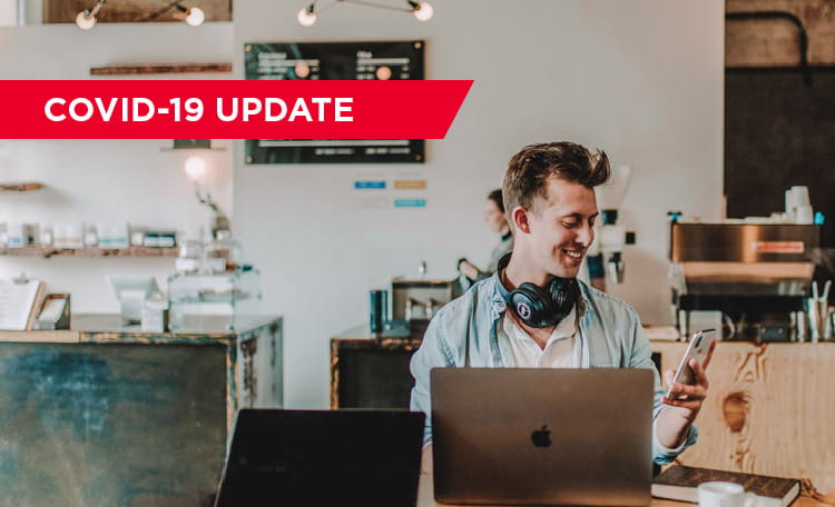 young white man working in cafe with laptop and headphones