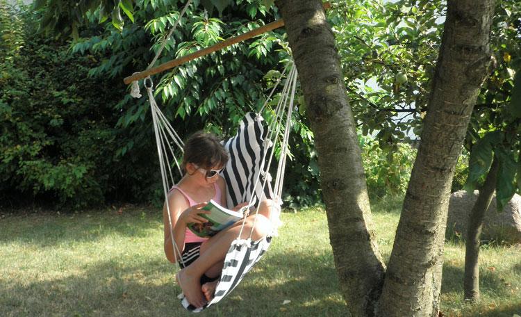 girl reading book in tree swing