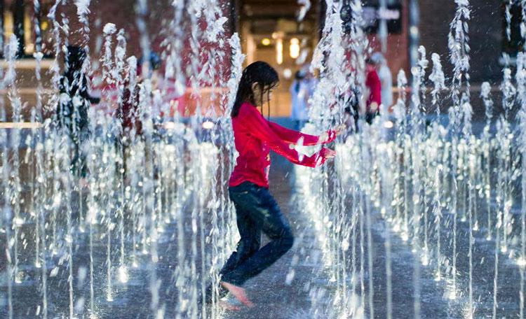 barefoot child running through street fountain lit at night