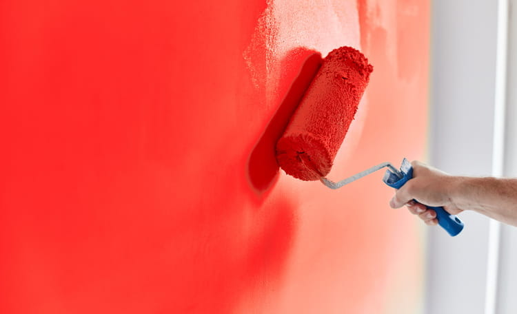 person painting wall red with a roller brush