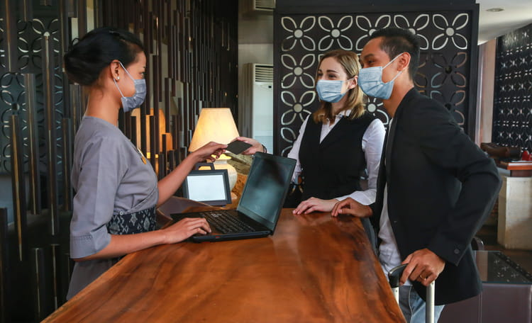 Hotel receptionist checking in guests all wearing PPE face masks