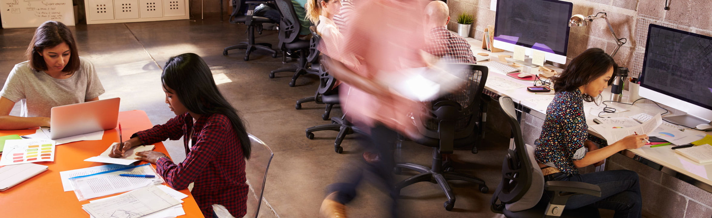 workers in coworking space blurred man walking past seated women